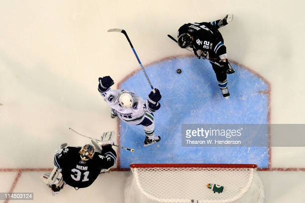Alex Burrows of the Vancouver Canucks celebrates after scoring in the third period as Antti Niemi and Dan Boyle of the San Jose Sharks look on in...