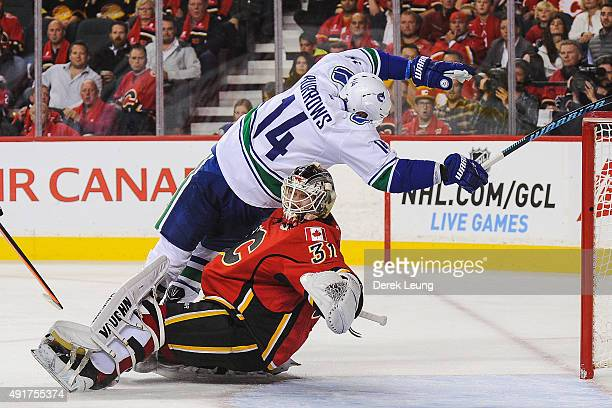 Alex Burrows of the Vancouver Canucks crashes the net of Karri Ramo of the Calgary Flames in the NHL season opener at Scotiabank Saddledome on...