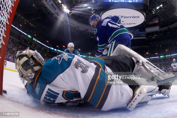 Alex Burrows of the Vancouver Canucks puts the puck on net as goaltender Antti Niemi of the San Jose Sharks makes a save and the puck goes just wide...