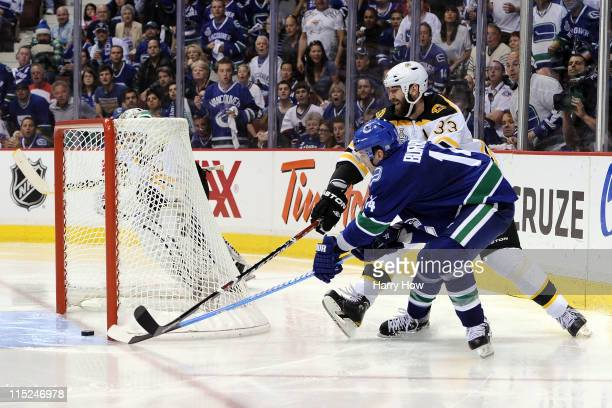 Alex Burrows of the Vancouver Canucks scores a goal in overtime against Zdeno Chara and Tim Thomas of the Boston Bruins to win Game Two of the 2011...