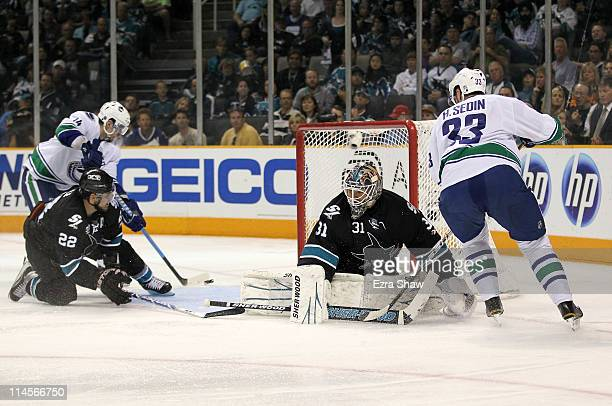 Alex Burrows of the Vancouver Canucks scores from the left wing on a pass from teammate Henrik Sedin through the crease past goaltender Antti Niemi...