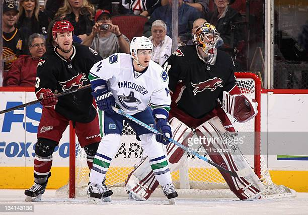 Alex Burrows of the Vancouver Canucks sets up in front of Derek Morris and goaltender Mike Smith of the Phoenix Coyotes during the NHL game at...