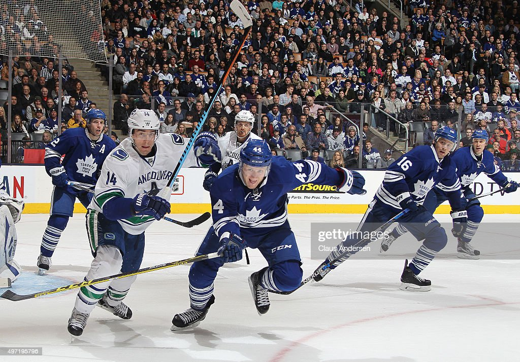 Alex Burrows #14 of the Vancouver Canucks skates against Morgan Rielly #44 of the Toronto Maple Leafs during an NHL game at the Air Canada Centre on November 14, 2015 in Toronto, Ontario, Canada. The Leafs defeated the Canucks 4-2.
