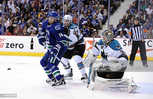 Alex Burrows of the Vancouver Canucks stands in the slot area for the deflection as MarcEdouard Vlasic and goaltender Antti Niemi of the San Jose...
