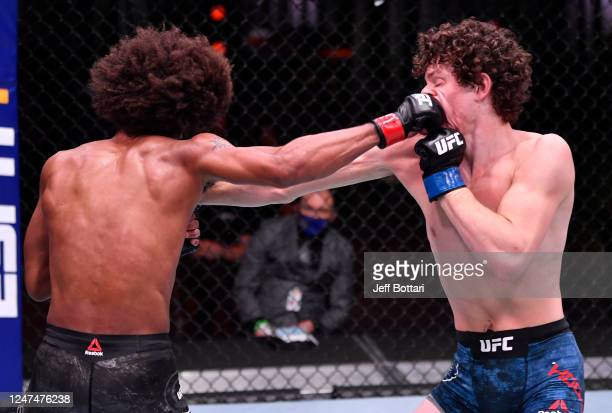 Alex Caceres punches Chase Hooper in their featherweight bout during the UFC 250 event at UFC APEX on June 06 2020 in Las Vegas Nevada
