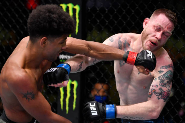 Alex Caceres punches Kevin Croom in a featherweight bout during the UFC Fight Night event at UFC APEX on February 27, 2021 in Las Vegas, Nevada.