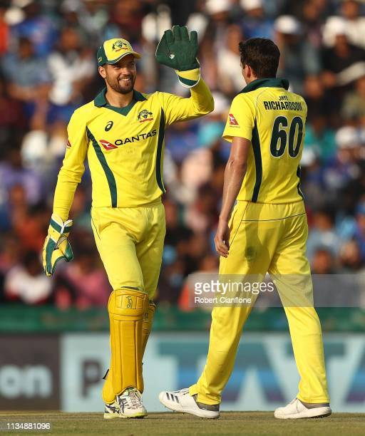 Alex Carey and Jhye Richardson of Australia celebrate taking the wicket of Bhuvneshwar Kumar of India during game four of the One Day International...