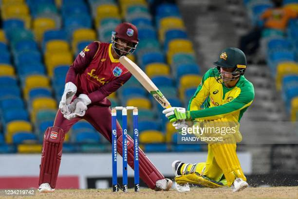 Alex Carey of Australia hits 4 and Shai Hope of West Indies watch during the 3rd and final ODI between West Indies and Australia at Kensington Oval,...