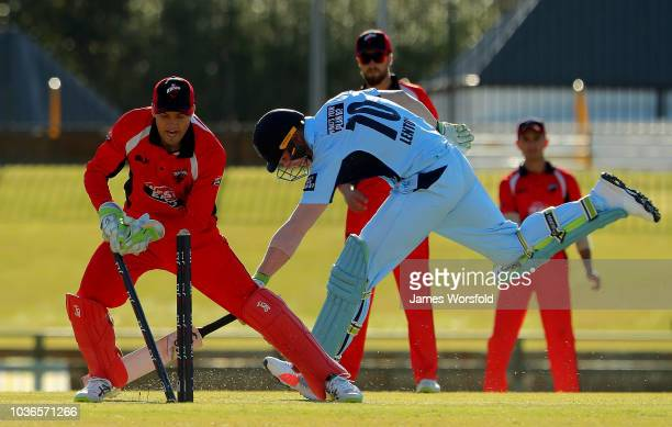 Alex Carey of SA tries to get a run out of Jay Lenton during the JLT One Day Cup match between South Australia and New South Wales at the WACA on...
