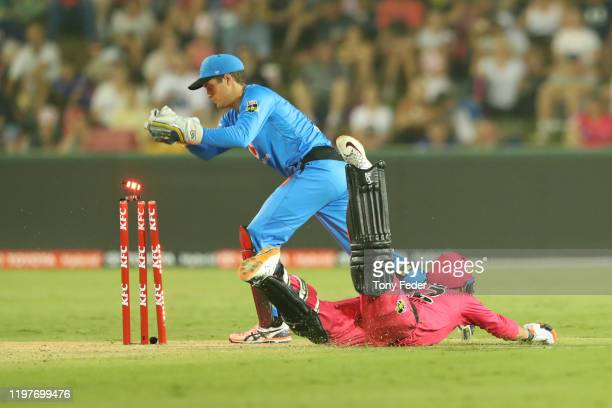 Alex Carey of the Adelaide Strikers attempts to run out Josh Philippe of the Sydney Sixers during the Big Bash League match between the Sydney Sixers...