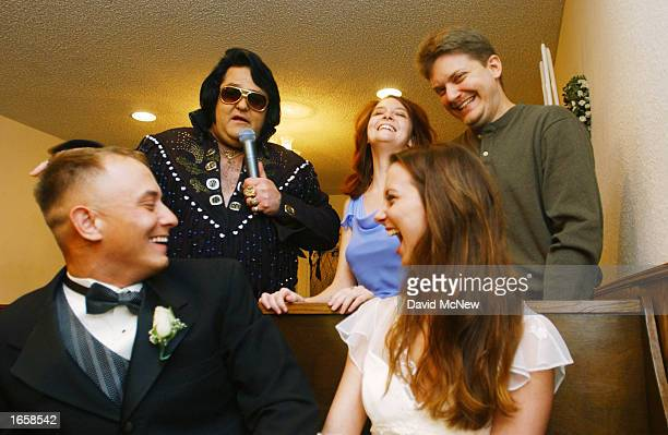 Alex Carlson a Marine from Twentynine Palms Marine Base California and his bride Gayle Barnett laugh as Elvis Presley impersonator Norm Jones...
