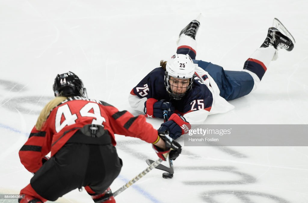 Alex Carpenter #25 of the United States controls the puck against Sarah Potomak #44 of Canada during the third period of the game on December 3, 2017 at Xcel Energy Center in St Paul, Minnesota. Canada defeated the United States 2-1 in overtime.