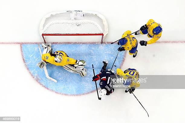 Alex Carpenter of the United States shoots and scores off the toe of Emilia Andersson of Sweden in the first period during the Women's Ice Hockey...