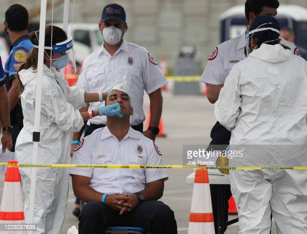 Alex Carrasquillo from the City of Miami FireRescue has a COVID19 swab test done at the Hard Rock Stadium testing site on May 06 2020 in Miami...