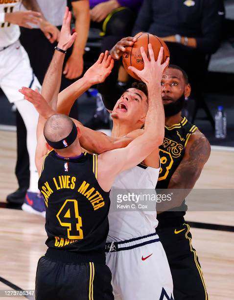 Alex Caruso of the Los Angeles Lakers and LeBron James of the Los Angeles Lakers strip the ball from Michael Porter Jr #1 of the Denver Nuggets...
