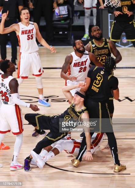 Alex Caruso of the Los Angeles Lakers attempts a shot as Jimmy Butler of the Miami Heat and Andre Iguodala of the Miami Heat defend during the third...