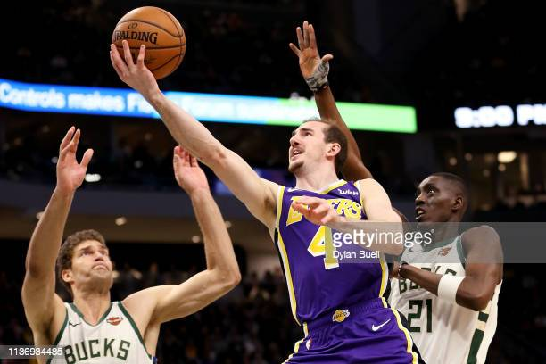 Alex Caruso of the Los Angeles Lakers attempts a shot while being guarded by Brook Lopez and Tony Snell of the Milwaukee Bucks in the fourth quarter...