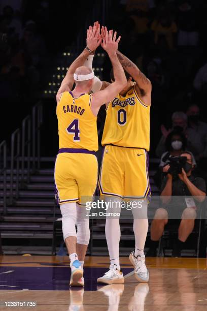 Alex Caruso of the Los Angeles Lakers high fives his teammate during the game against the Phoenix Suns during Round 1, Game 3 of the 2021 NBA...
