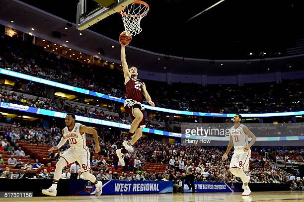 Alex Caruso of the Texas AM Aggies goes up for a dunk between Jordan Woodard and Isaiah Cousins of the Oklahoma Sooners in the first half in the 2016...