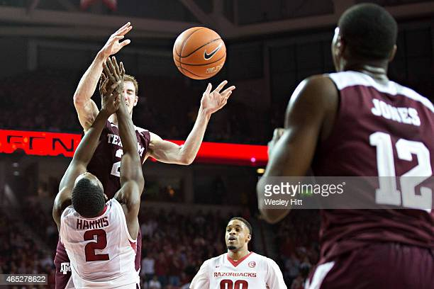 Alex Caruso passes the ball to Jalen Jones of the Texas AM Aggies while being defended by Alandise Harris of the Arkansas Razorbacks at Bud Walton...