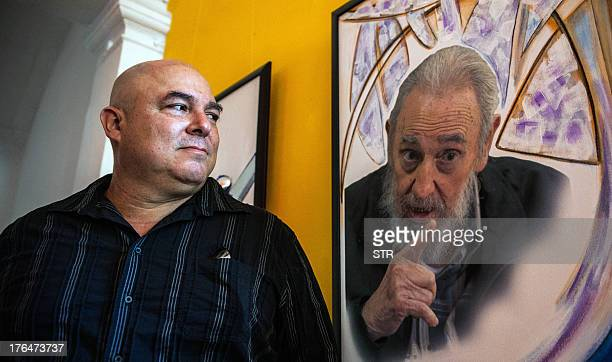 Alex Castro son of Cuban leader Fidel Castro stands next to a painting depicting his father during the opening of an exhibition to celebrate Fidel's...