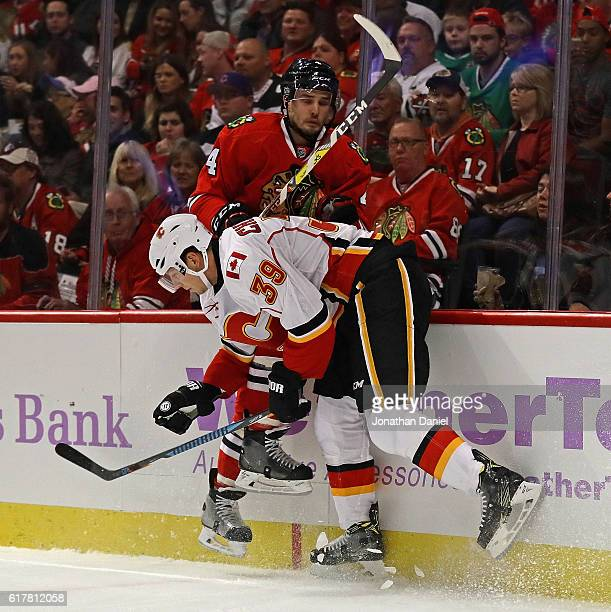 Alex Chiasson of the Calgary Flames checks Niklas Hjalmarsson of the Chicago Blackhawks into the boards at the United Center on October 24 2016 in...