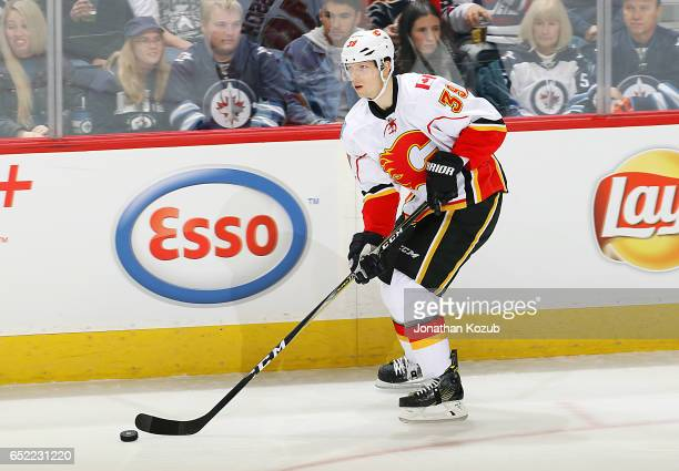 Alex Chiasson of the Calgary Flames plays the puck down the ice during first period action against the Winnipeg Jets at the MTS Centre on March 11...