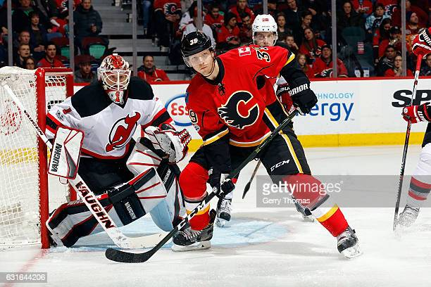 Alex Chiasson of the Calgary Flames skates against Keith Kinkaid of the New Jersey Devils during an NHL game on January 13 2017 at the Scotiabank...