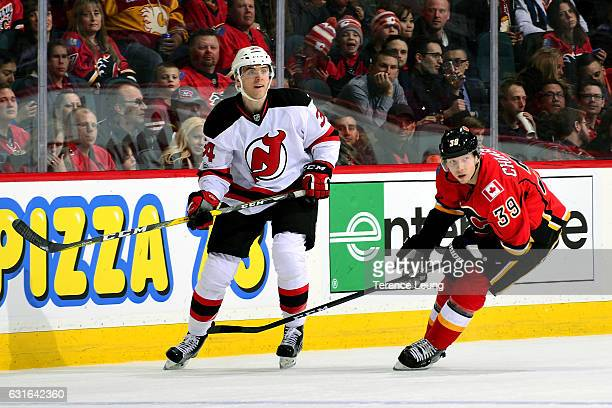 Alex Chiasson of the Calgary Flames skates against Steven Santini of the New Jersey Devils during an NHL game on January 13 2017 at the Scotiabank...