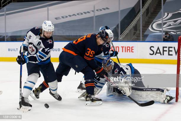 Alex Chiasson of the Edmonton Oilers battles against Josh Morrissey, Neal Pionk and goaltender Connor Hellebuyck of the Winnipeg Jets at Rogers Place...