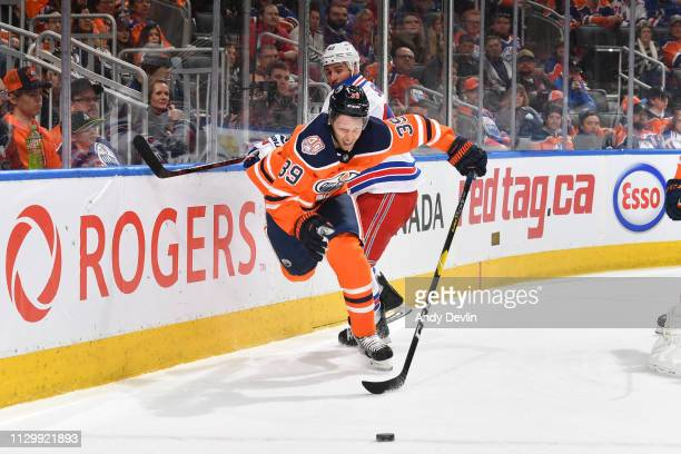 Alex Chiasson of the Edmonton Oilers battles for the puck against Brendan Smith of the New York Rangers on March 11 2019 at Rogers Place in Edmonton...