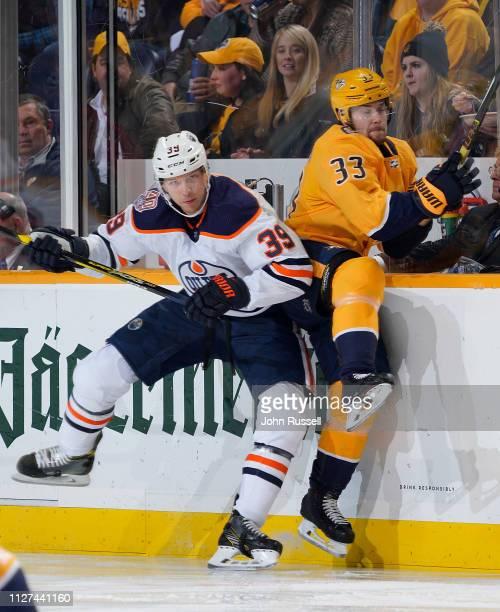Alex Chiasson of the Edmonton Oilers checks Viktor Arvidsson of the Nashville Predators at Bridgestone Arena on February 25 2019 in Nashville...