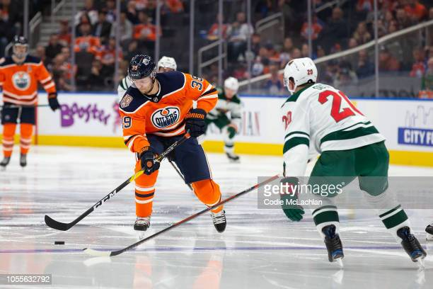Alex Chiasson of the Edmonton Oilers skates the puck in against Ryan Suter of the Minnesota Wild at Rogers Place on October 30 2018 in Edmonton...