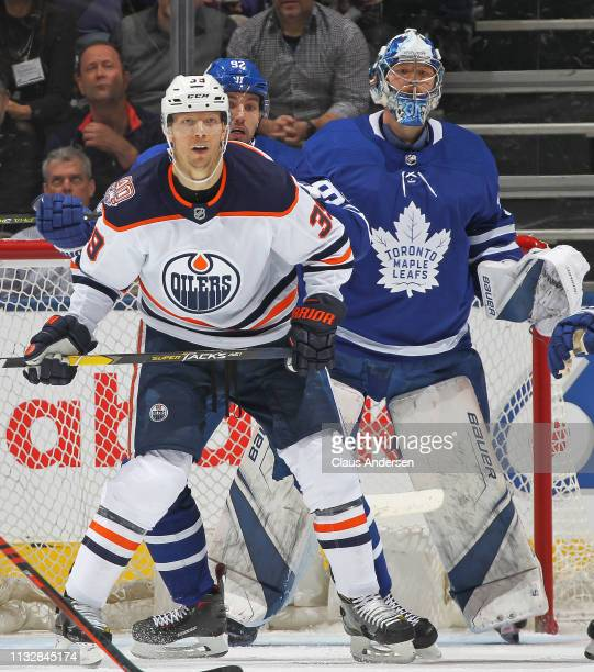 Alex Chiasson of the Edmonton Oilers waits for a puck to tip in front of Igor Ozhiganov and Frederik Andersen of the Toronto Maple Leafs during an...
