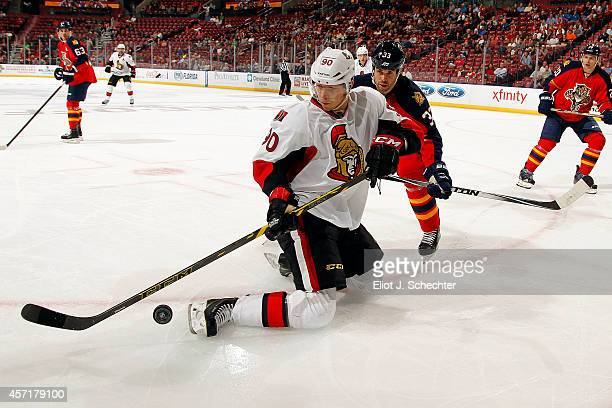Alex Chiasson of the Ottawa Senators attempts to control the puck against Willie Mitchell of the Florida Panthers during the second period at the BBT...
