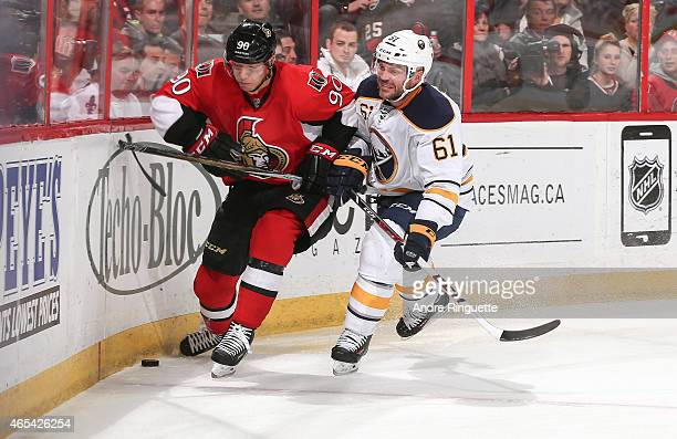 Alex Chiasson of the Ottawa Senators controls the puck along the end boards against pressure from Andre Benoit of the Buffalo Sabres at Canadian Tire...