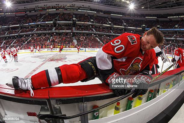 Alex Chiasson of the Ottawa Senators stretches on the boards during warmup prior to a game against the Detroit Red Wings at Canadian Tire Centre on...