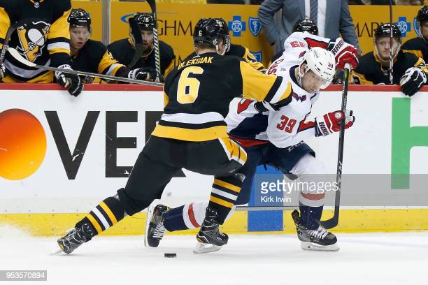Alex Chiasson of the Washington Capitals attempts to skate the puck past Jamie Oleksiak of the Pittsburgh Penguins during the third period in Game...