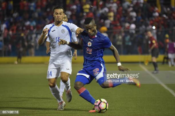 Alex Christian of Haiti vies for the ball with Eulises Pavon of Nicaragua during the first of two match to define the last qualified to the 2017 Gold...