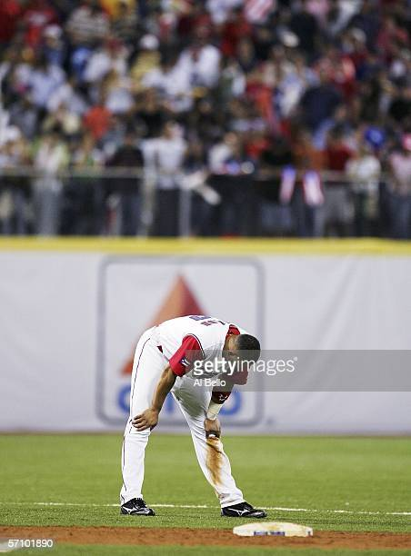 Alex Cintron of Puerto Rico hangs his head after hitting into a double play with two men in scoring position in the eighth inning against Cuba during...