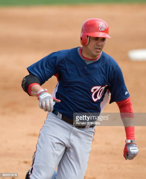 Alex Cintron of the Washington Nationals rounds third base against the Florida Marlins during a spring training game at Roger Dean Stadium on March...