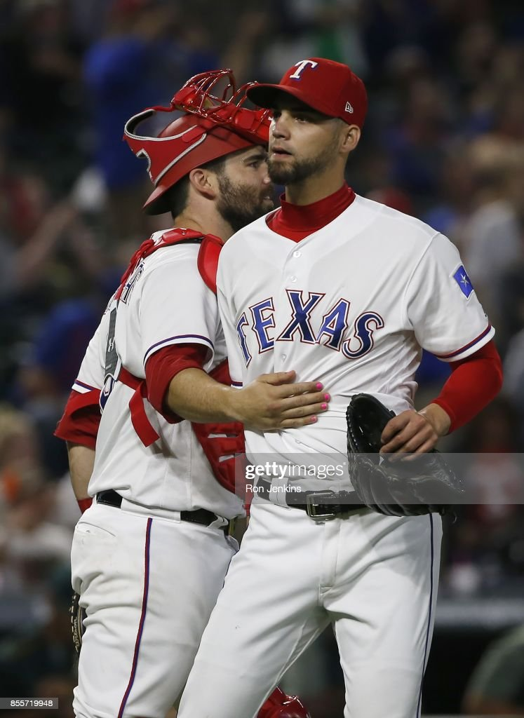 Alex Claudio #58 and Brett Nicholas #6 of the Texas Rangers celebrate following the team's win over the Oakland Athletics at Globe Life Park in Arlington on September 29, 2017 in Arlington, Texas. The Rangers won 5-3.