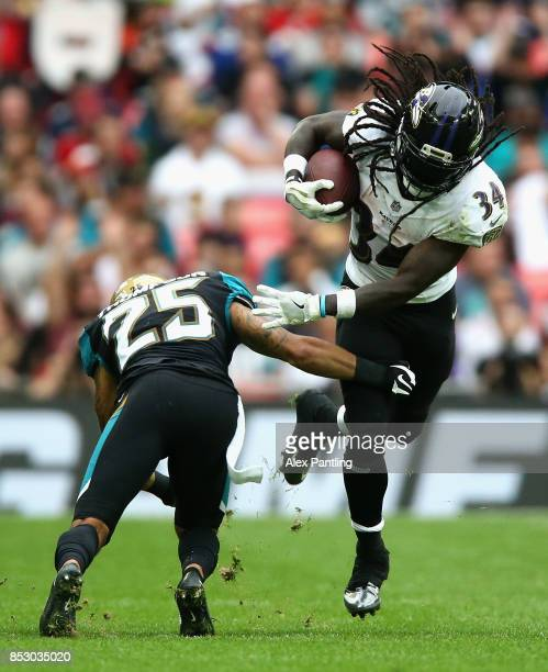 Alex Collins of Baltimore Ravens goes past Peyton Thompson of the Jacksonville Jaguars during the NFL International Series match between Baltimore...