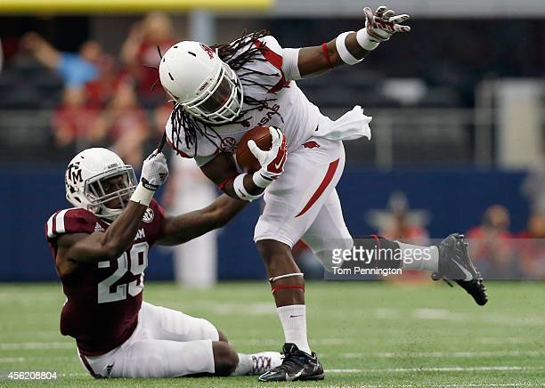 Alex Collins of the Arkansas Razorbacks carries the ball against Deshazor Everett of the Texas A&M Aggies in the firs half of the Southwest Classic...