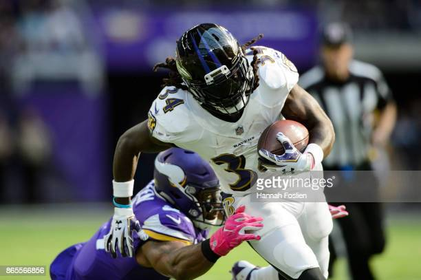 Alex Collins of the Baltimore Ravens carries the ball against Everson Griffen of the Minnesota Vikings during the game on October 22 2017 at US Bank...