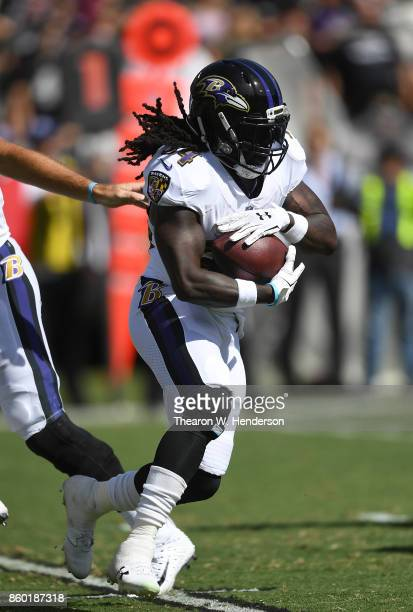 Alex Collins of the Baltimore Ravens carries the ball against the Oakland Raiders during the first quarter of their NFL football game at...