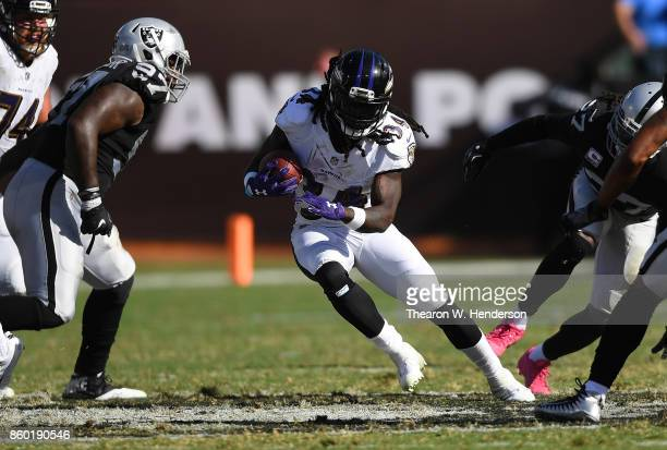 Alex Collins of the Baltimore Ravens carries the ball against the Oakland Raiders during the fourth quarter of their NFL football game at...