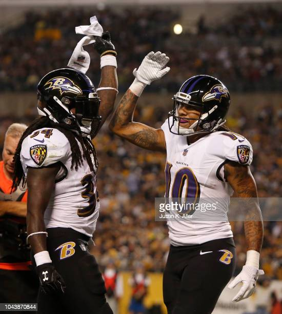 Alex Collins of the Baltimore Ravens celebrates with Chris Moore after a 3 yard touchdown reception in the first quarter of the game against the...