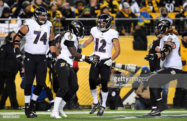 Alex Collins of the Baltimore Ravens celebrates with teammates after rushing for a 18 yard touchdown in the second quarter during the game against...