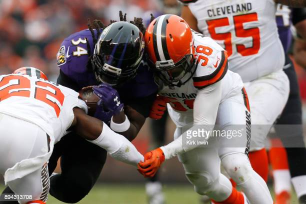 Alex Collins of the Baltimore Ravens collides with Christian Kirksey of the Cleveland Browns in the first half at FirstEnergy Stadium on December 17...
